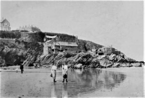 A view from the foreshore of the fish cellar 'Good Intent' with 'Fly' cellar to the right. The Atlantic Hotel, built in 1892, is in the background, therefore the photograph was taken after it was built, possibly about 1910. Two young woman are standing in the foreground. Photographer: Ennor.