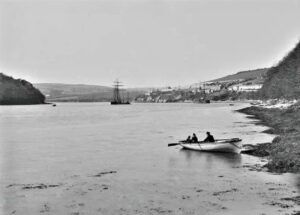 """A view of Malpas, in the distance, from the Tresillian River. A number of schooners are moored off Malpas and a rowing boat """"Busybody"""" with a man and two of children is in the foreground. Photographer: Unknown."""